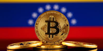 Physical version of Bitcoin (new virtual money) and Venezuela Flag.