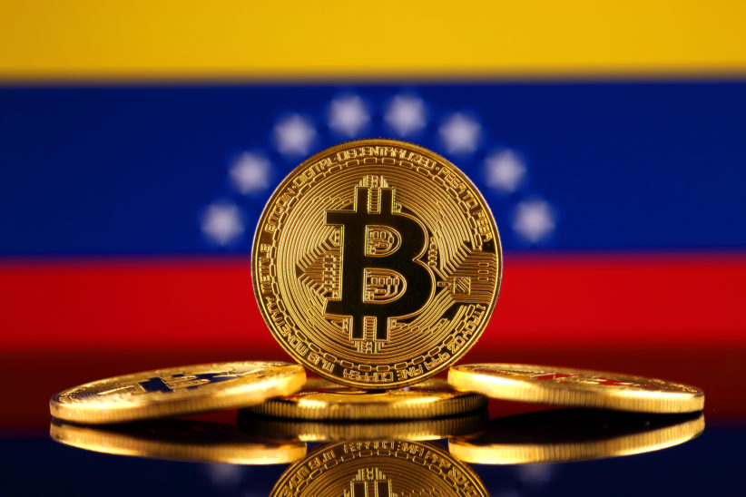 Physical version of Bitcoin (new virtual money) and Venezuela Flag.
