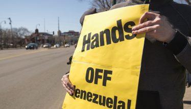 Protester holds sign opposing US intervention in Venezuela
