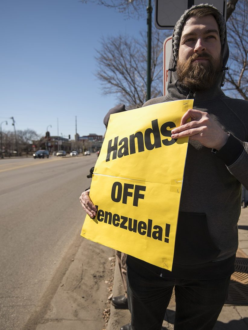 Protester holds sign opposing US intervention in Venezuela