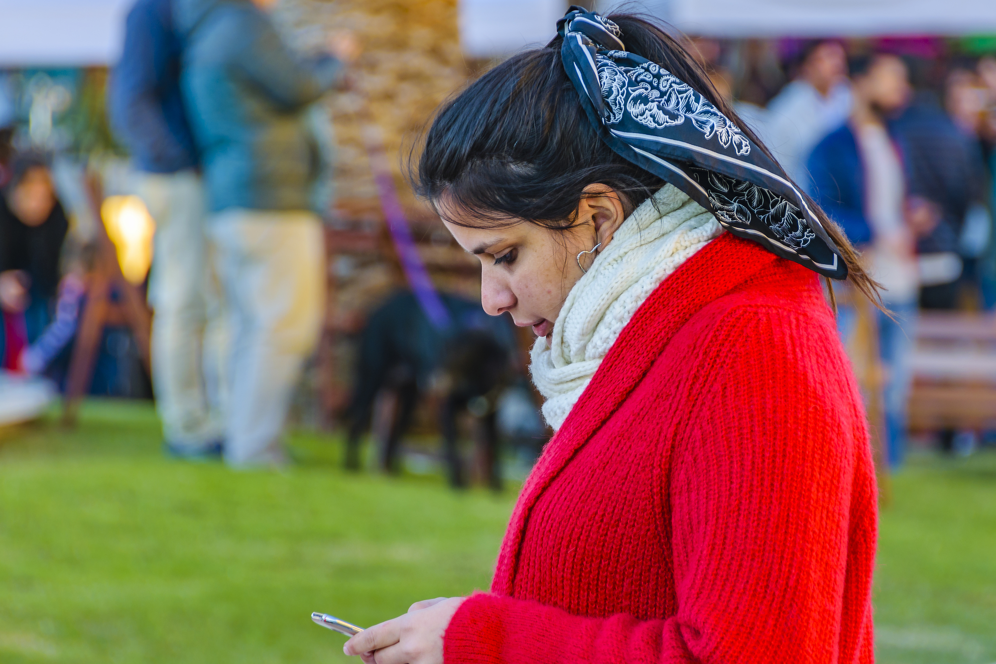 Young woman watching her cellphone at urban outdoor street fair, montevideo city, uruguay