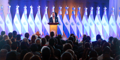 Najib Bukele presenting his government plan in front of a backdrop of Salvadoran flags