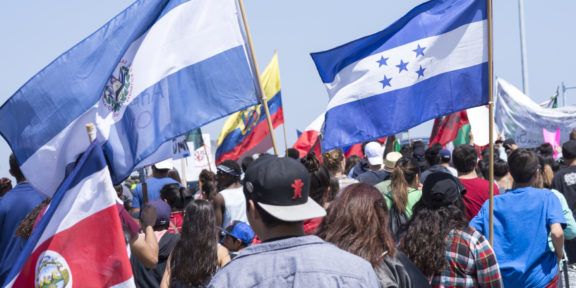 Protesters gather to march against Donald Trump outside a Trump rally in San Diego while carrying flags from Costa Rica, El Salvador, Honduras and other Central American nations.