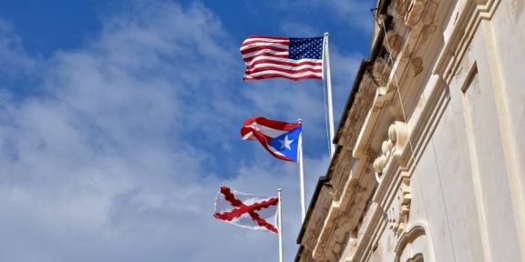 The American flag flies over the flag of Puerto Rico on top of a colonial building