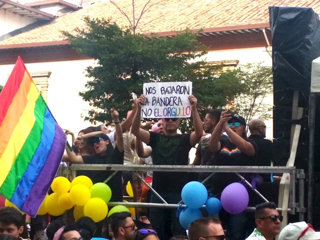 At Medellin Gay Pride a man holds a sign.
